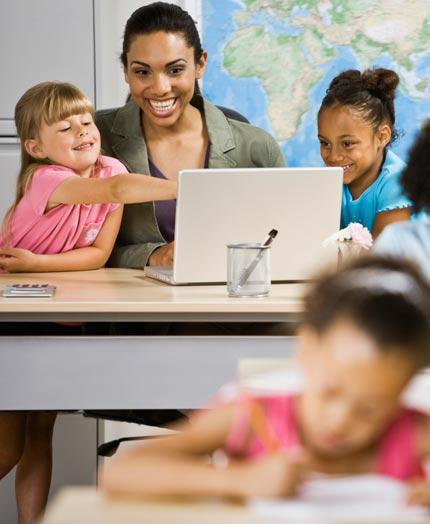 African Amerian teacher with two 3rd grade children on a laptop computer