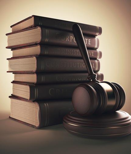 stack of legal book wth a gavel leaning against it
