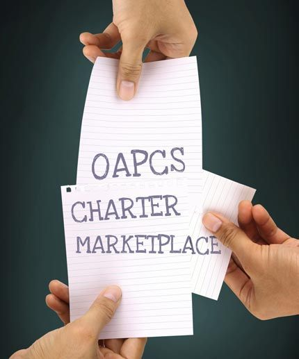 hands holding 3 pieces of paper together spelling out OAPCS Charter Marketplace